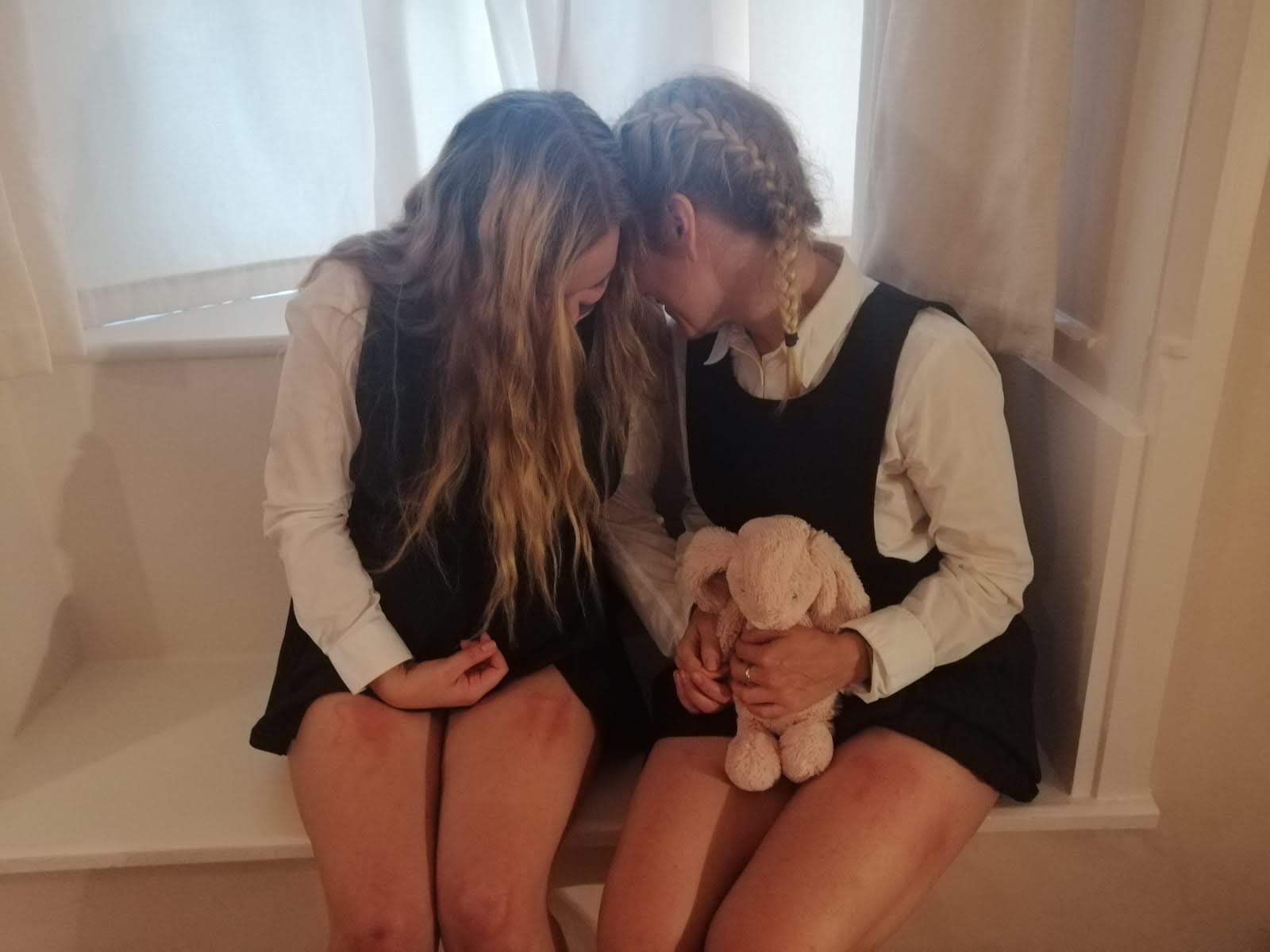 2 blonde adult school girls in navy pinafores and long sleeved white shrits sharing whispers