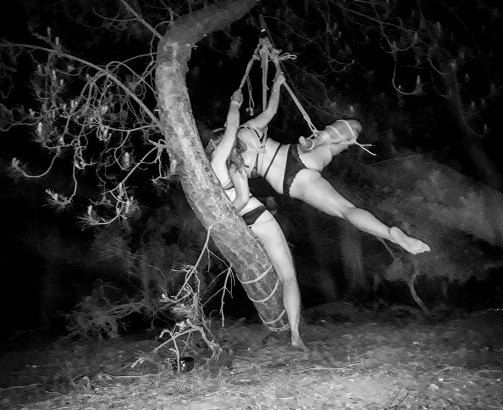 Black and White image of two girls tied in a tree