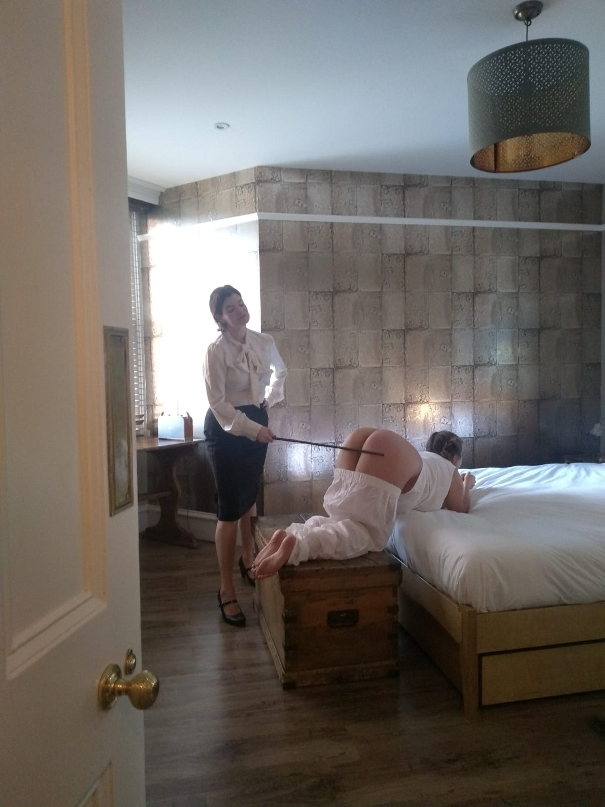 White pjs high arch on bed, Miss Mathew in pencil skirt caning bare bottom